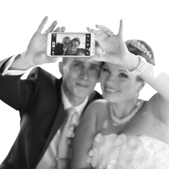 Young just married couple taking pictures of themselves by smart